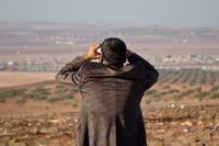 En man riktar sin kikare mot Kobane.