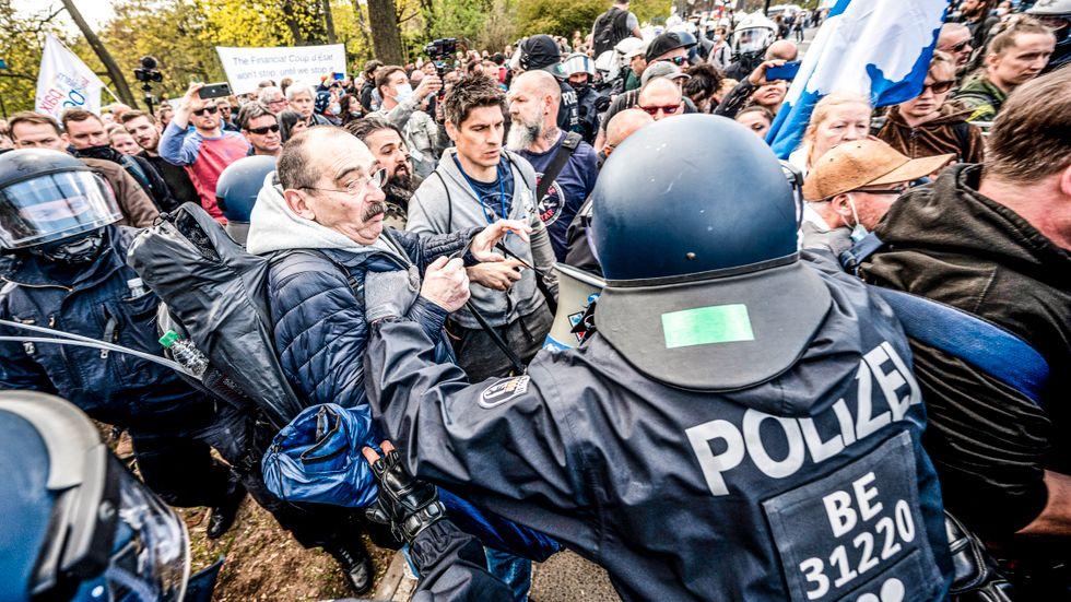 Polis griper in mot en demonstration mot coronarestriktioner utanför riksdagshuset i Berlin, säte för tyska Förbundsdagen.