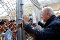 EU:s asyl- och migrationskommissionär Dimitris Avramopoulos talar med boende i det stora flyktinglägret Moria på grekiska ön Lesbos. Arkivbild.