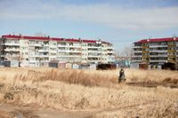 En kvinna håller för munnen och promenerar mellan husen i östra Sibirien.