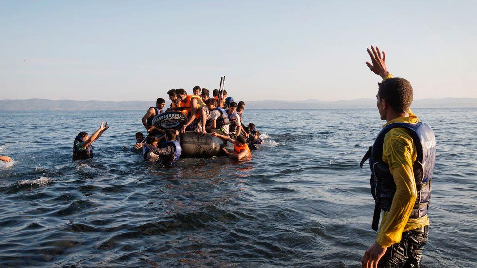 En grupp syriska flyktingar har fått bensinstopp och tvingas paddla mot land. Efter fem timmar på havet andländer de utmattade men lättade. (Klicka för att se fler bilder)