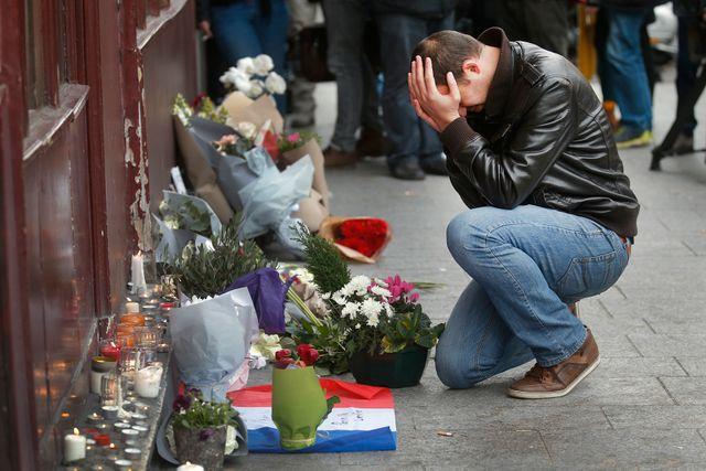 En man visar sin sorg utanför restaurangen Le Carillon på lördagsmorgonen.