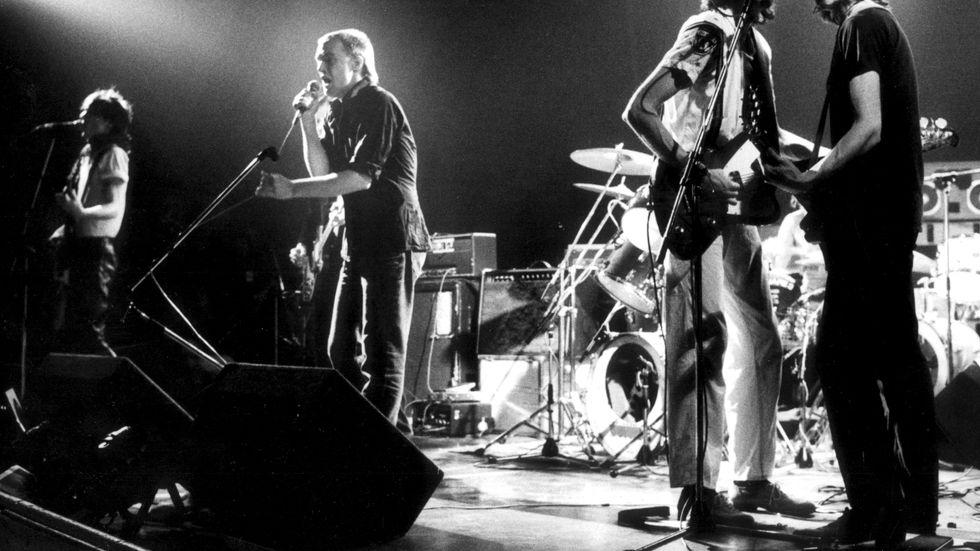 """Ebba Grön och Dag Vag i Eriksdalhallen i Stockholm 1980. Thåström och Gurra från Ebba Grön tillsammans med Stig Vig och Zilverzurfarn från Dag Vag öser loss med """"Staten och kapitalet""""."""