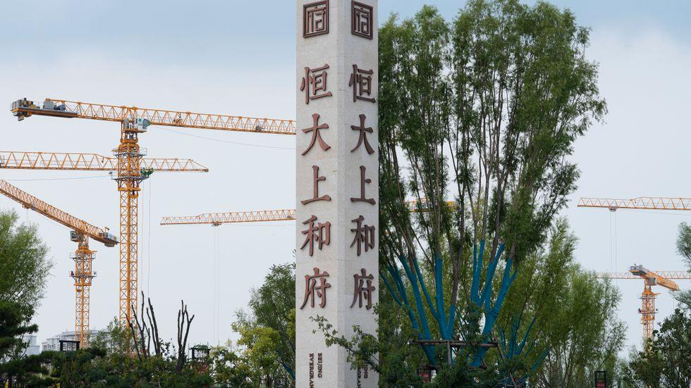 Byggkranar syns bakom en skylt med Evergrandes namn och logga vid en byggarbetsplats i Peking.