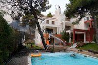 En man häller ut vatten från poolen i ett försök att hindra lågorna som närmar sig hans hus att få fäste, 35 kilometer norr om Aten.