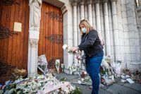 En kvinna lägger ner en blomma framför Notre Dame i Nice, på fredagen. Nicebon Klas Andersson bor alldeles intill.