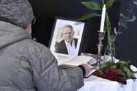 En kondoleansbok bredvid ett tänt ljus och ett fotografi på Benny Fredriksson på Kulturhuset i Stockholm.