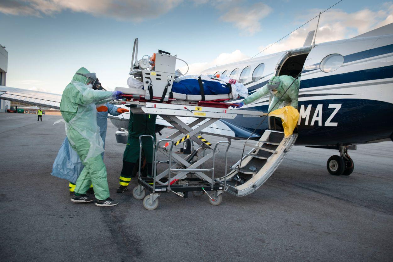 Gustaf Schröder, Johnny Lindblad och Daniel Herbertsson flyttar långsamt patienten från flygplanet till den väntande ambulansen. SvD har som enda journalister fått följa hur en patient intensivvårdas i flyg och sedan i specialambulans.