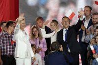 Andrzej Duda, frun Agata Kornhauser-Duda och dottern Kinga vinkar till supportrar. Dudas seger i det polska valet kan leda till nya konflikter med EU-kommissionen.