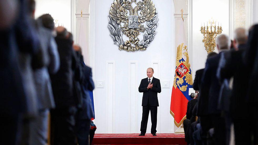 Ryske presidenten Vladimir Putin applåderar vid en ceremoni i Kreml den 12 juni.