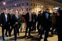 Rysslands president Vladimir Putin på väg med blommor till attentatsplatsen.