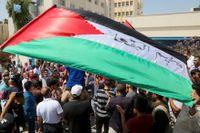 Palestinska flyktingar håller upp flaggor och skanderar mot USA:s beslut att strypa bidrag till FN:s organ för palestinska flyktingar (UNRWA). Protesten ägde rum i Amman i Jordanien i söndags.