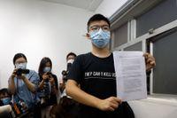 Demokratiaktivisten Joshua Wong håller upp det dokument som visar att han diskvalificerats från att ställa upp i valet som nu skjutits upp.