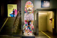 """Pireuslejonet, ett monument i Historiska museets entréhall, har fått en virkad one-piece av konstnären Elisabeth Bucht i utställningen """"History unfolds"""", där konstnärer fått gå i dialog med samlingarna."""
