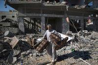 En palestinsk man räddar tillhörigheter från ett hus som förstörts av en attack.