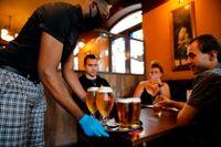 En servitör med skyddshandskar och munskydd serverar öl på lördagen till förväntansfulla gäster på en pub i Stratford i östra London.