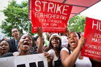 Demonstranter utanför en McDonalds-restaurang i New York. Demonstranterna visar sitt stöd för snabbmatsarbetarnas krav på högre löner, fackliga rättigheter och bättre villkor.