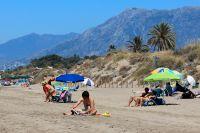 Turister solar på en badstrand i Malaga.