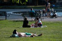 Människor solar och svalkar sig vid fontänen i Tessinparken i Stockholm nyligen – i helgen lär det åter bli en vanlig syn.
