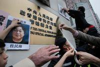 Demonstranter sätter upp bilder på försvunna bokhandlare utanför People's Government i Hong Kong. Gui Minhai, en av de försvunna, på bilden till vänster.