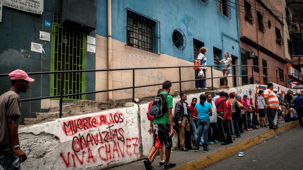 Den politiska debatten förs överallt i Venezuela. Här på en vägg där en graffiti till stöd för Chávez målats över med en emot. Samtidigt köar människor för att få handla livsmedel till reglerade priser i en av de statliga matvarubutikerna.
