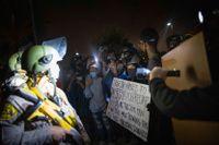 Demonstranter och poliser under protester i det område i södra Los Angeles där en 29-årig man sköts ihjäl av polis i tisdags.