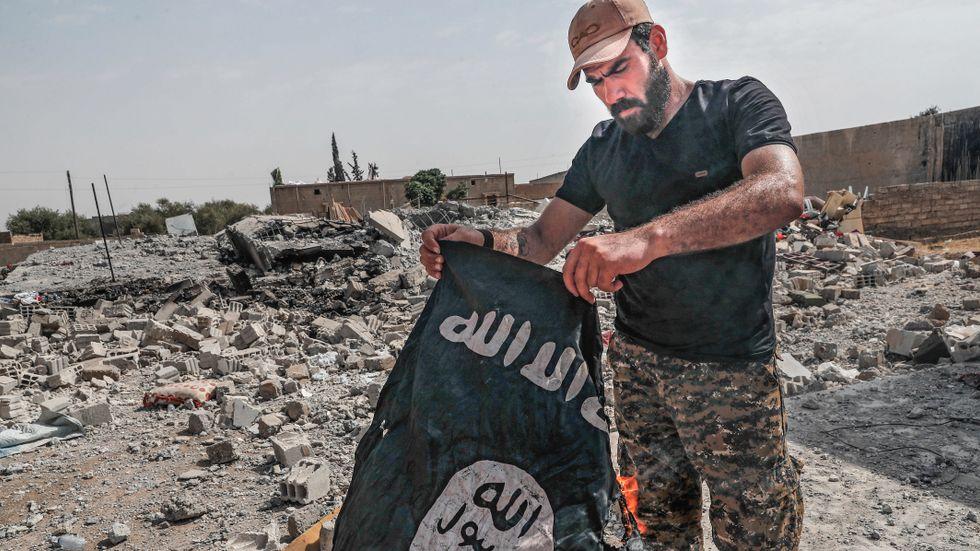 Soldat bränner en IS-flagga. Arkivbild.