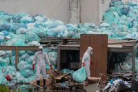 Vårdarbetare i skyddsutrustning slänger sopor utanför ett sjukhus i delstaten Veracruz i Mexiko, där covid-patienter behandlas.