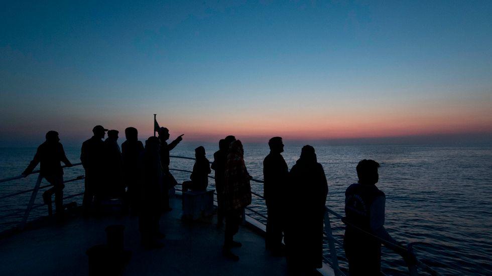 Migranter ombord på ett räddningsfartyg blickar mot Sicilien. Arkivbild.
