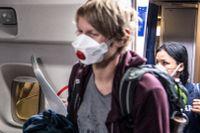 En flygvärdinna i mask tar emot passagerare på Frankfurts flygplats den 8 april.