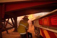 En brandman söker skydd under en brandbil i släckningsarbetet vid branden utanför Perth.