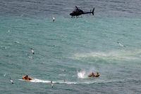 Polis och räddningspersonal i en helikopter öppnade enligt vittnen eld mot hajen men lyckades inte stoppa det dödliga angreppet, och det var oklart om hajen dödades.