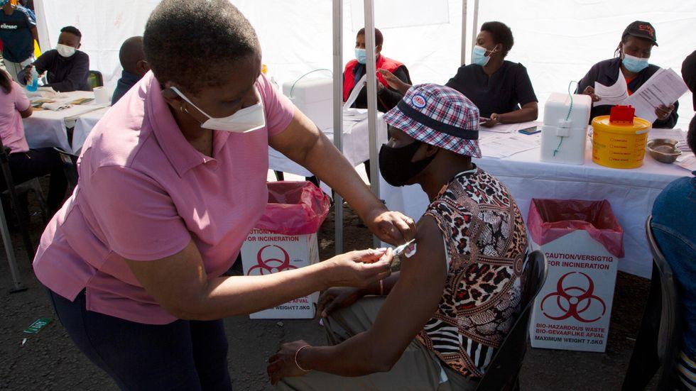 En sköterska delar ut en dos covidvaccin i Soweto i Sydafrika. Bild från augusti.