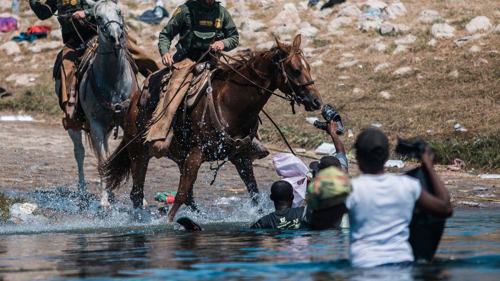 Gränspolisen försöker hindra migranter från att korsa gränsfloden Rio Grande in i USA.