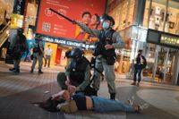 Kravallpolis i Hongkong griper en demonstrant under en protest den 12 juni.