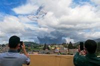Två indonesiska män tar foton på Mount Sinabung utbrott.