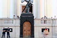 """Poliser och en rättighetsaktivist utanför en kyrka i Warszawa i augusti. Utanför samma kyrka har högerextremister samlats under hösten för att """"skydda"""" den katolska kyrkan i landet. Arkivbild."""
