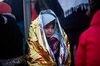 En flyktingpojke värmer sig efter familjens ankomst till den grekiska ön Lesbos. Inför EU:s toppmöte på torsdag och fredag har det utbrutit ett internt EU-bråk om hur man ska göra med flyktingarna som kommer till Europa.