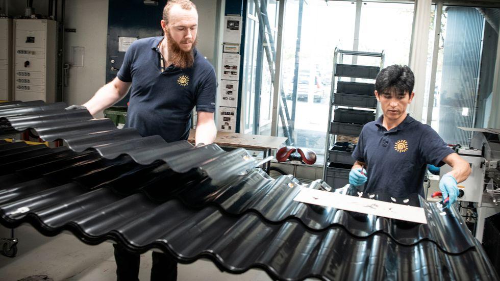 Plåttak med integrerade solceller. Muhammed Rasuli Karl Yngström lägger en sista hans på panelerna på svenska Midsummer.