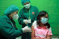 En flicka vaccineras med det kinesiska Sinovacs vaccin mot covid-19 i staden Medan på norra Sumatra i Indonesien. Bilden är från i juli.
