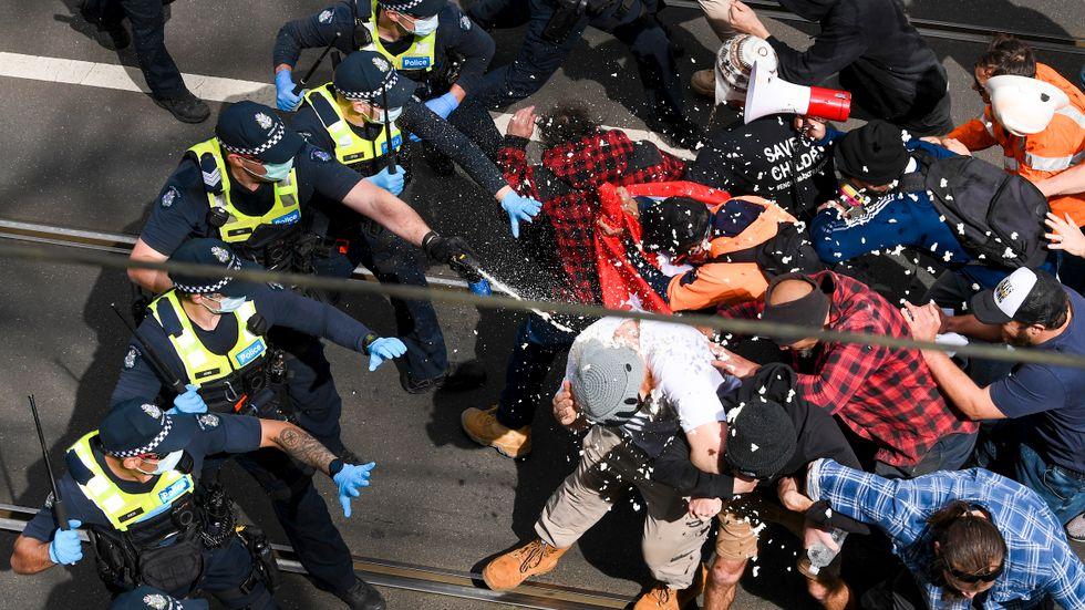 Polisen i Melbourne använder pepparsprej under sammandrabbningen på lördagen.
