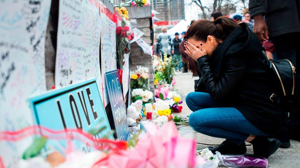 En kvinna kämpar för att hålla tårarna tillbaka vid en minnesplats efter dådet i Toronto.