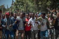 Anhängare till aktivisten Jawar Mohammed skanderar slagord till stöd för honom utanför hans hem i Addis Abeba i torsdags.