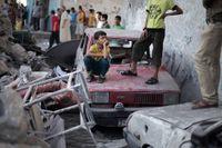 Palestinier utanför ett hus som förstörts i en israelisk flygattack.