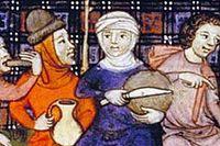 En resande grupp äter en enkel gemensam måltid, 1300-tal.