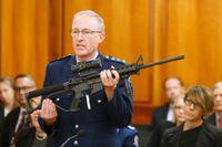 Poliskommissarien Mike McIlraith visar upp ett vapen, av samma typ som användes av gärningsmannen vid moskéattackerna i Christchurch, i det nyzeeländska parlamentet i april.