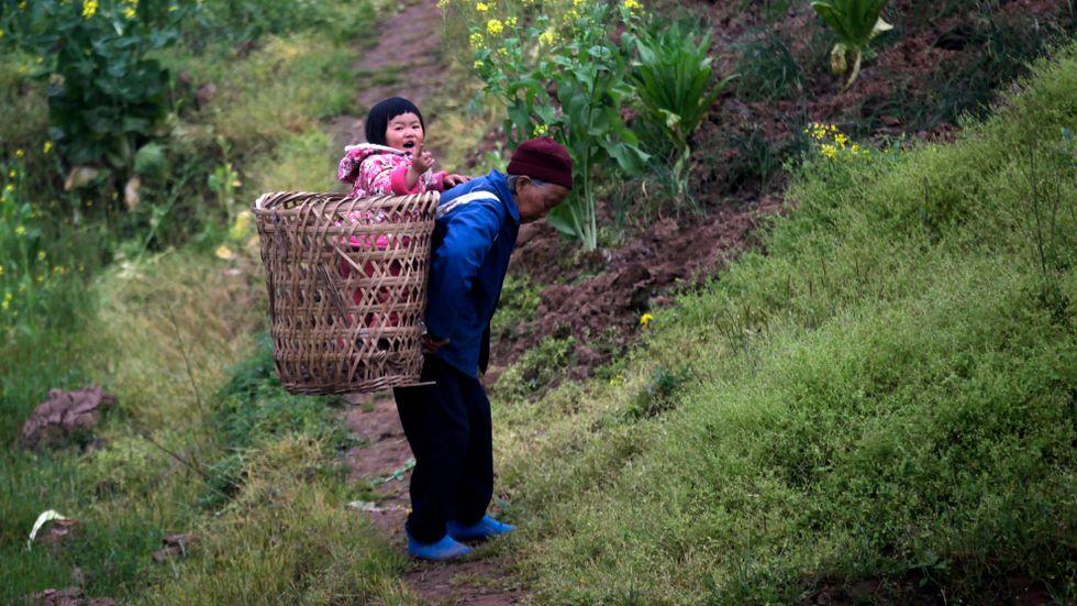 Kinas mycket hårda ettbarnspolitik har successivt luckrats upp. Här ses en äldre kvinna bära på ett barn utanför Chongqing. Arkivbild.