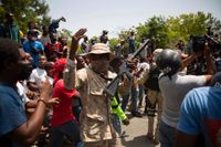 Poliser vid en samling människor som protesterar mot mordet på Haitis president.