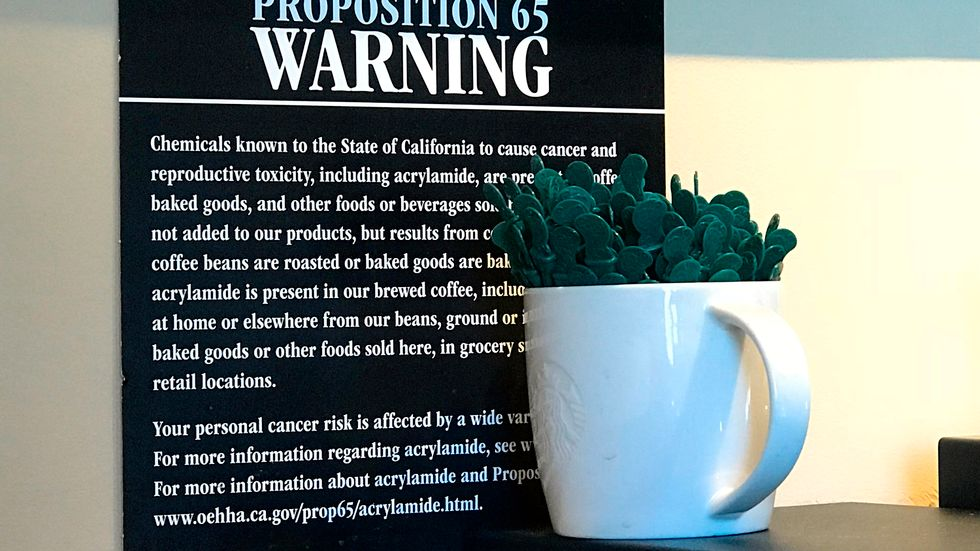 """This March 30, 2018 file photo shows a Proposition 65 warning sign behind a coffee mug at a Starbucks coffee shop in Burbank, Calif. California has officially concluded coffee does not pose a """"significant"""" cancer risk. State regulators gave final approval Monday, June 3, 2019 to a rule that means coffee won't have to carry ominous warnings that the beverage may be bad for you."""