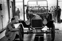 Bilprovare Randolf Nordström, elegant i förmansrock, besiktigar en T-Ford från 1914 på ny nyinvigda bilprovningsanläggningen i Vällingby.  En strålkastare hängde snett – och nervdaller hos ägaren. Men bilen godkändes.